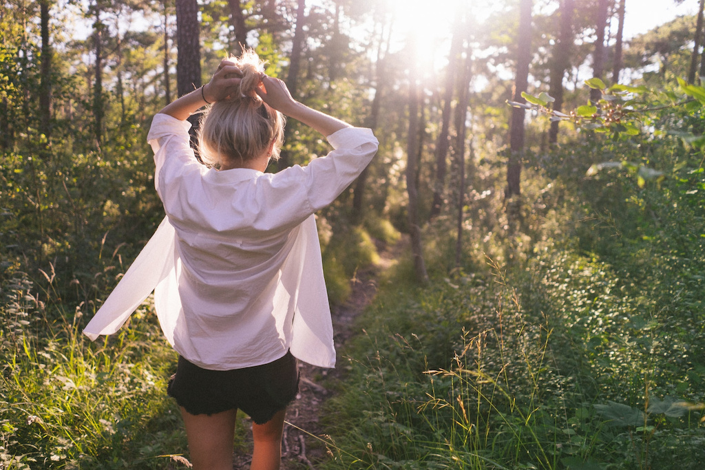 Woman in white shirt, a travel wardrobe essential, in the woods