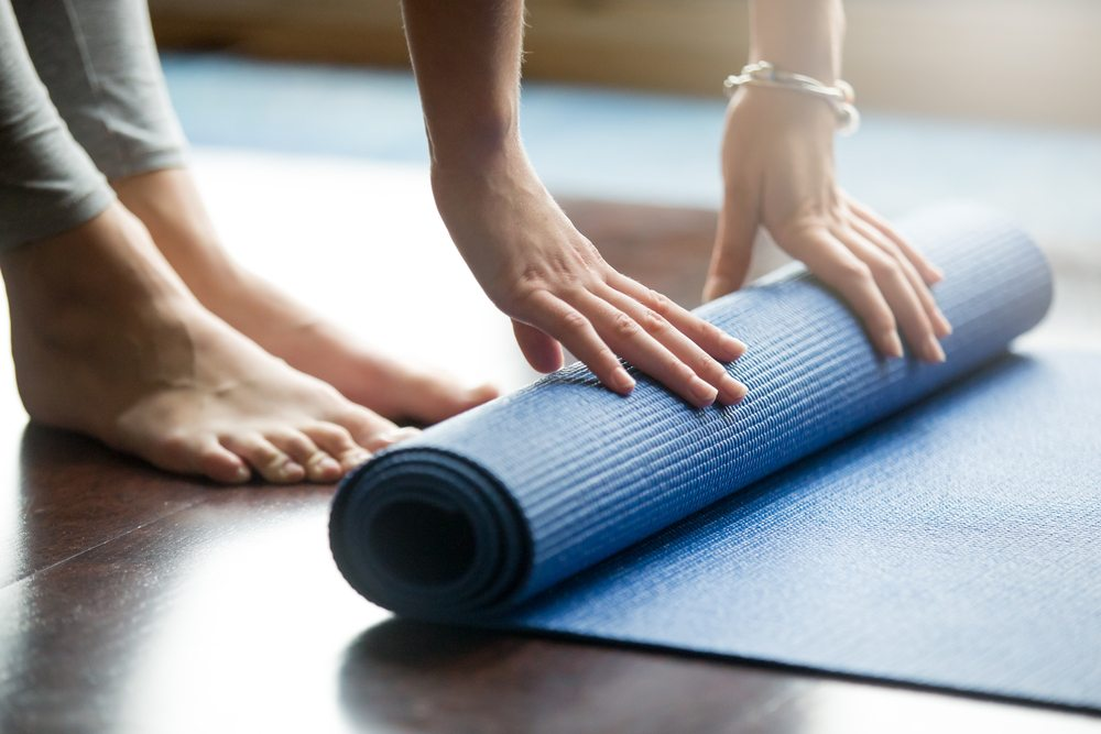 rolling out a yoga mat the first step before trying a yoga move for beginners