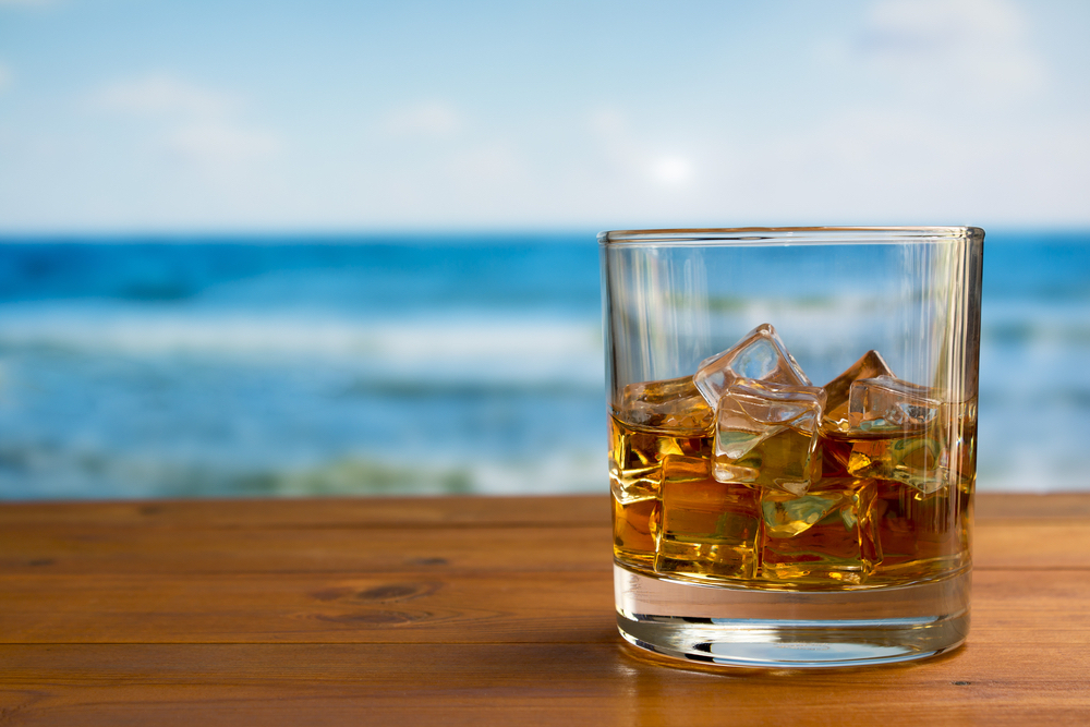 whiskey on the rocks with beach in background, a simple whiskey cocktail for summer