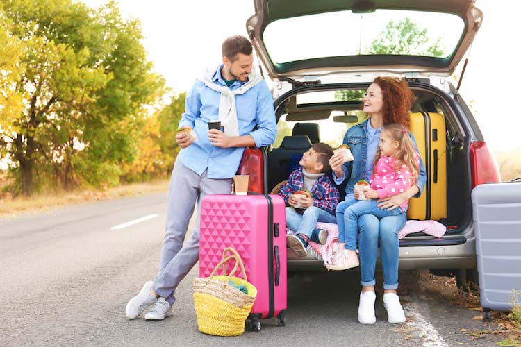 traveling family enjoying healthy travel snacks outside of their car