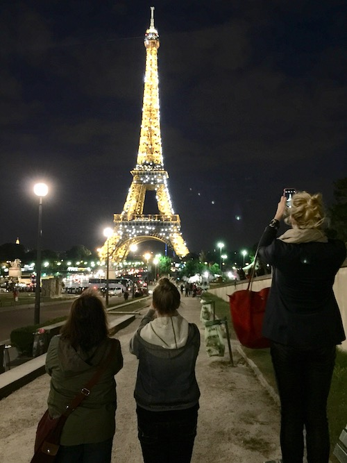 The Eiffel Tower in Paris at night, a popular summer family bucket list destination.