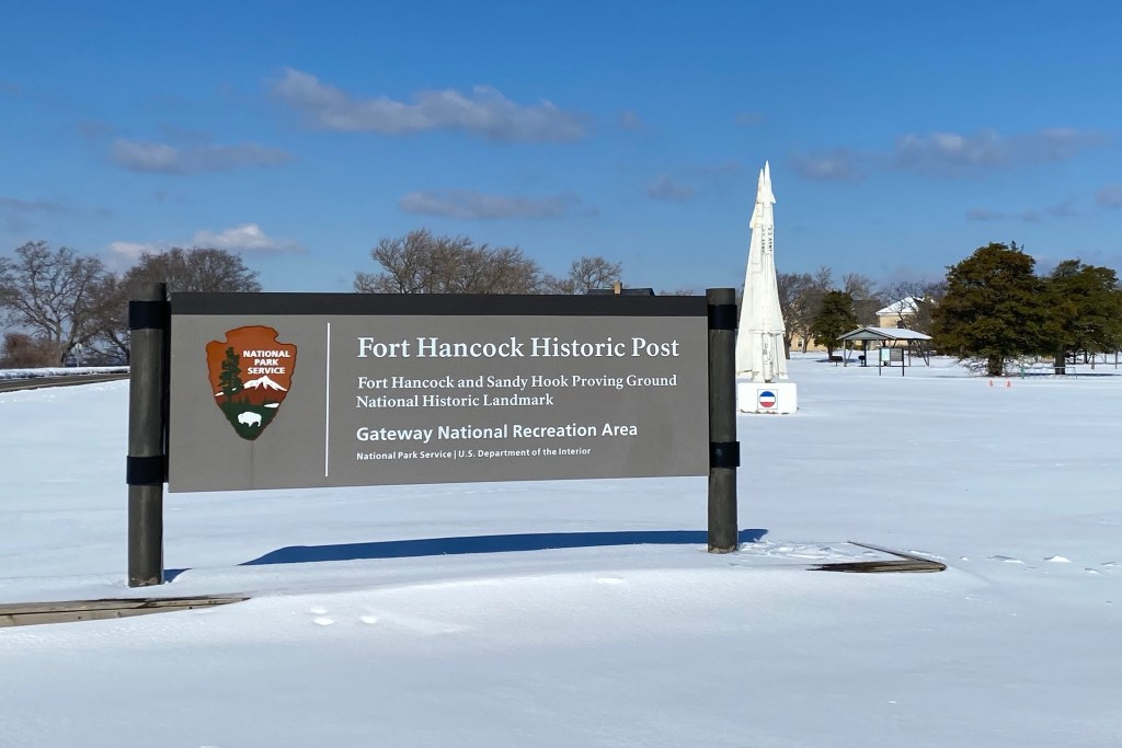 Fort Hancock Historic Post welcome sign with missile behind it at Sandy Hook NJ beach