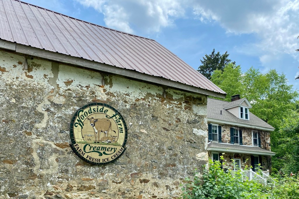natural stone wall with logo for Woodside Creamery, a homemade ice cream stand in Delware, one of the fun things to do
