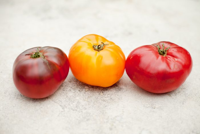 Three tomatoes on a marble surface to be used in Pasta with Tomatoes and Lemon