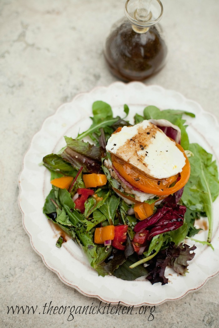 The Caprese Stack Salad on white plate with bottle of balsamic vinaigrette