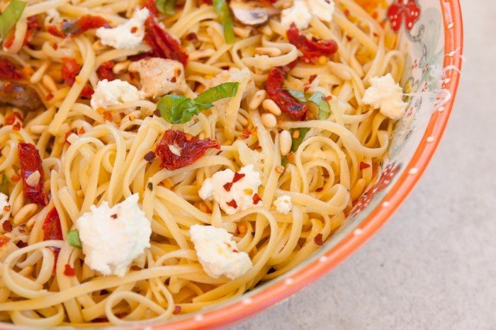 A close up photo Linguini with Chicken and Goat Cheese #linguini in an orange bowl set on grey stone backdrop