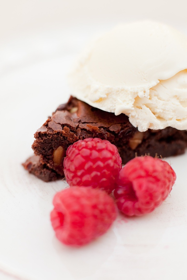 A close of of brown butter brownies with macadamia nuts with ice cream and berries