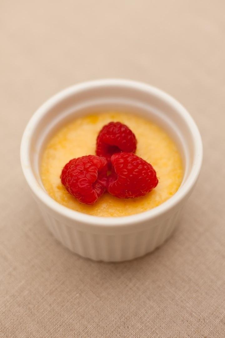 Orange Vanilla Creme Brulee in a white ramekin topped with fresh raspberries
