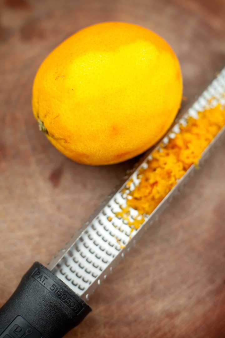 An orange with a microplane full of orange zest on a cutting board