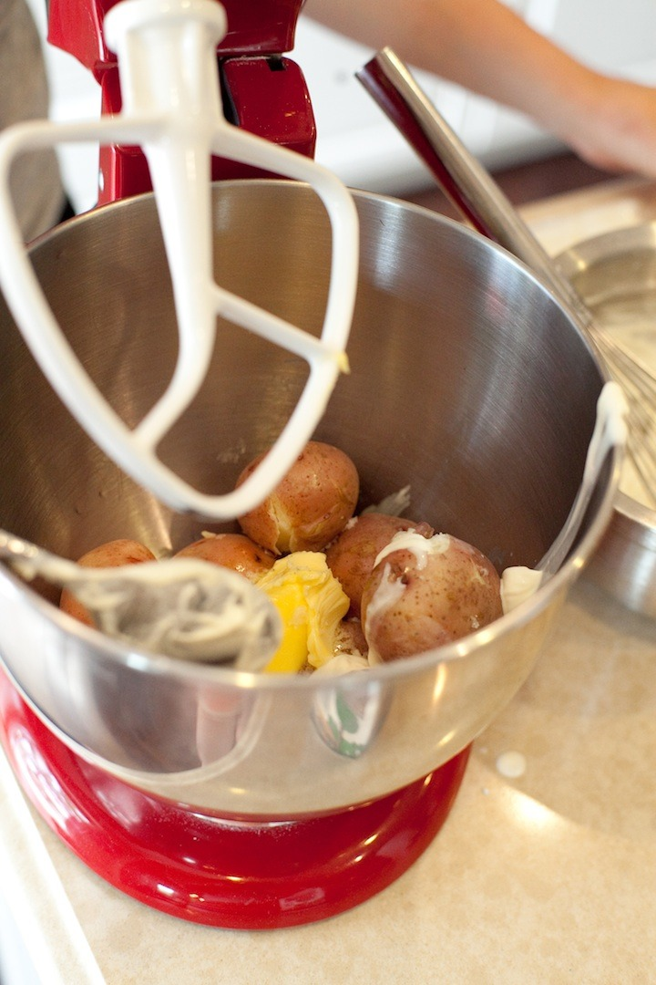 A stand mixer with new red potatoes and butter in the bowl to be used in Decadent Smashed Potatoes