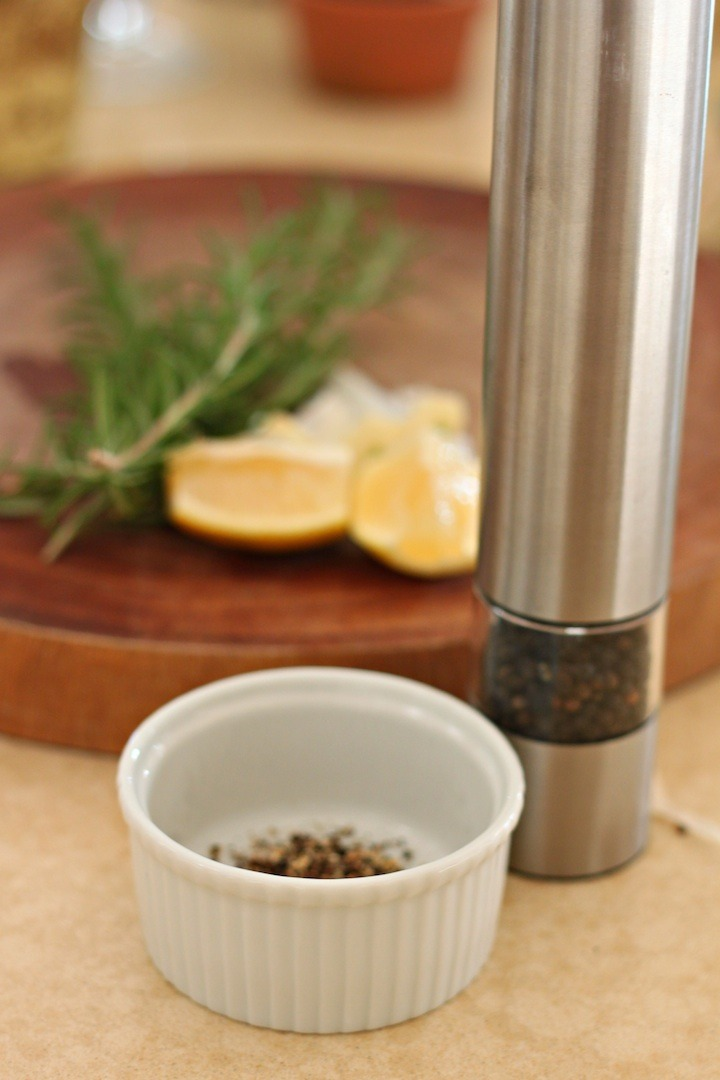 A white ramekin and pepper grinder in front of a cutting board with lemon slices and rosemary springs to be used in Roasted Lemon/Garlic Chicken with Shallots