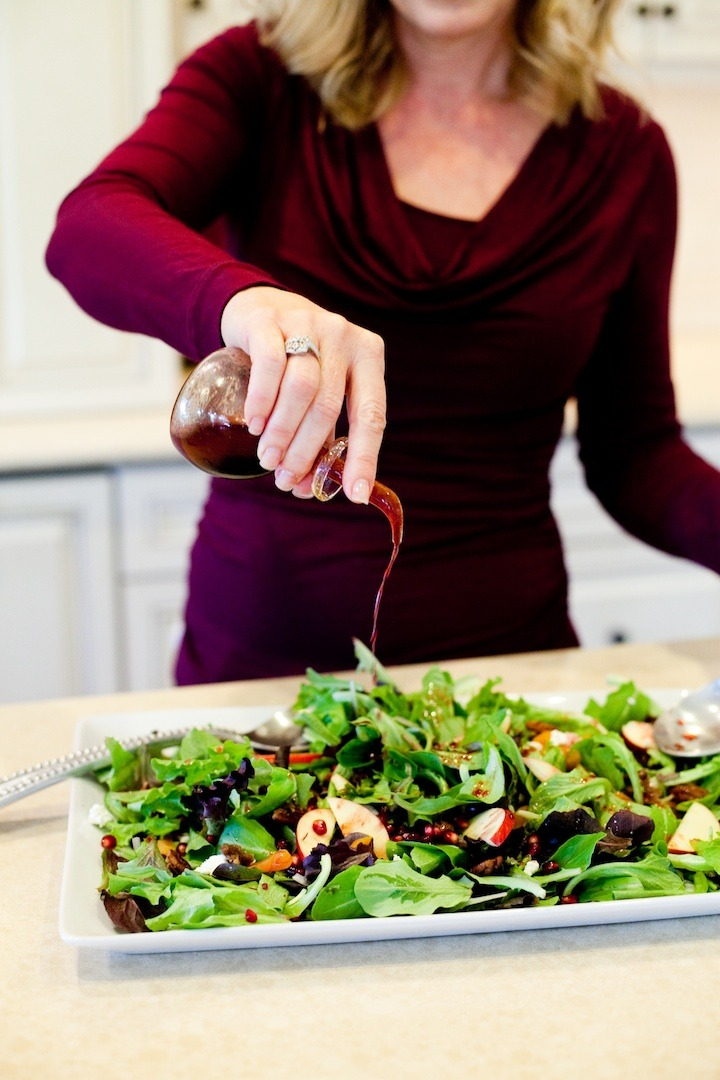 A blonde woman dressing a platter of Greens with Pomegranate Vinaigrette
