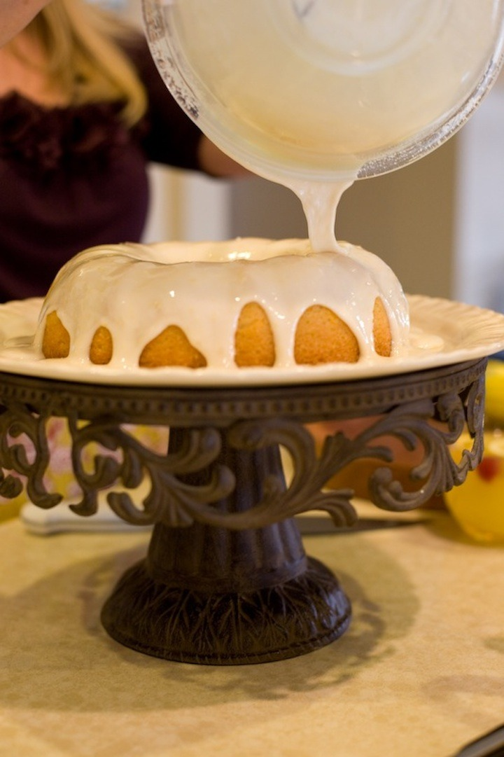 A woman pouring glaze over Orange Cranberry Pound Cake on a fancy cake plate