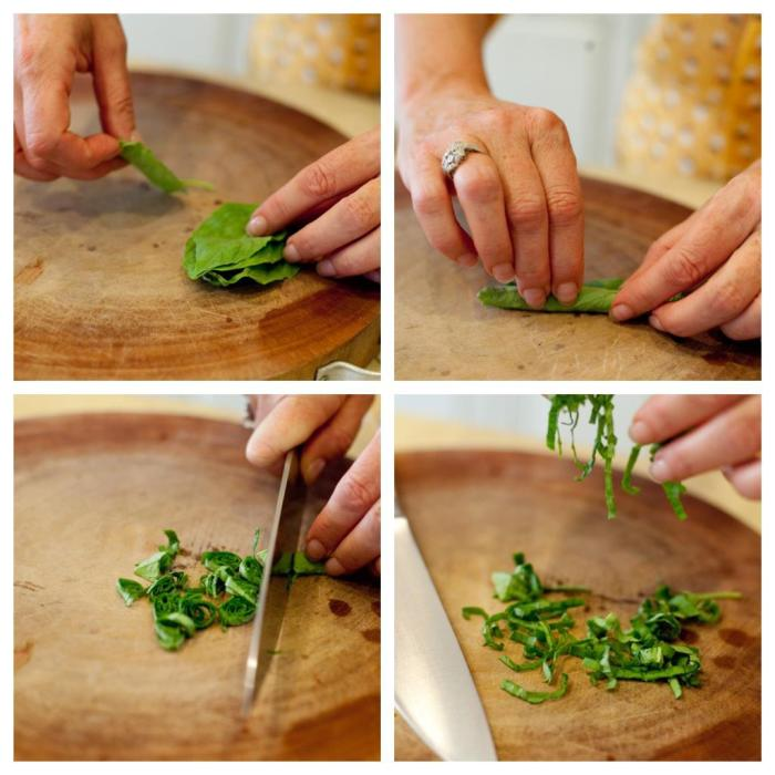 A females hands demonstrating how to chiffonade basil for use in Easy Tomato Bruschetta