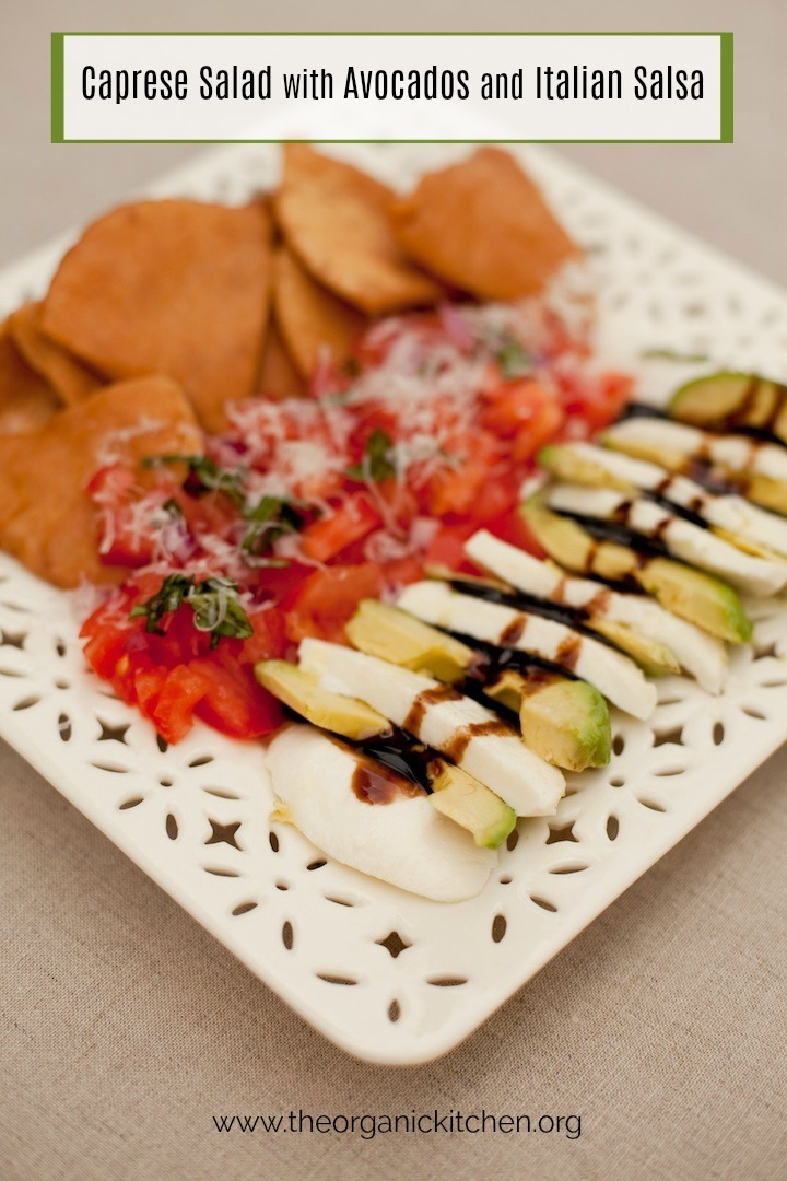 A white plate on beige table cloth filled with Caprese Salad with Avocados and Italian Salsa
