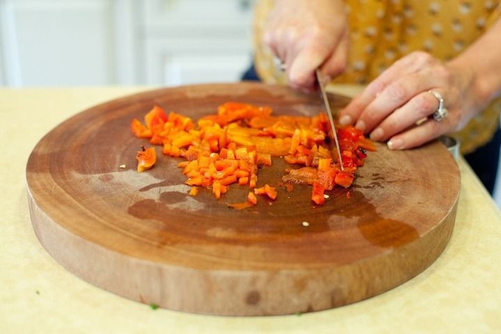How to Roast a Red Bell Pepper: a woman's hands dicing roasted red bell pepper