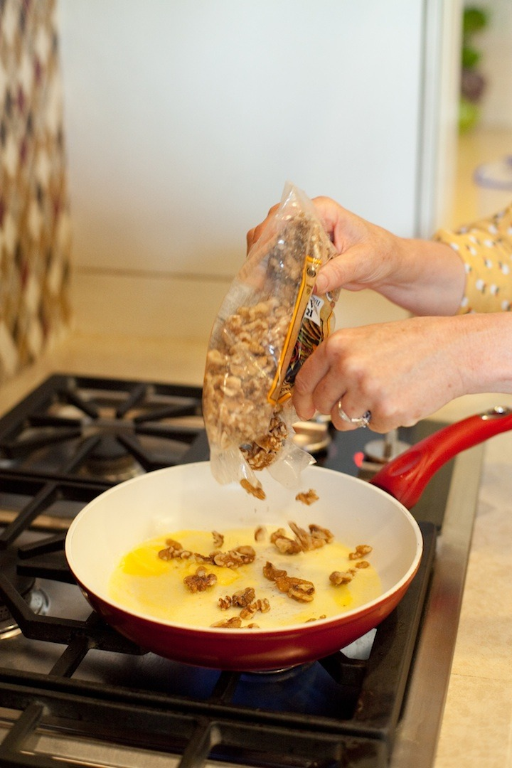 A female's hands pouring walnuts into a pan of melted butter to demonstrate How to Caramelize Nuts