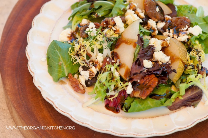 """Greens with Asian Pears and Fig/Maple Balsamic Vinaigrette"" served on a \white plate set on a wooden cutting board"