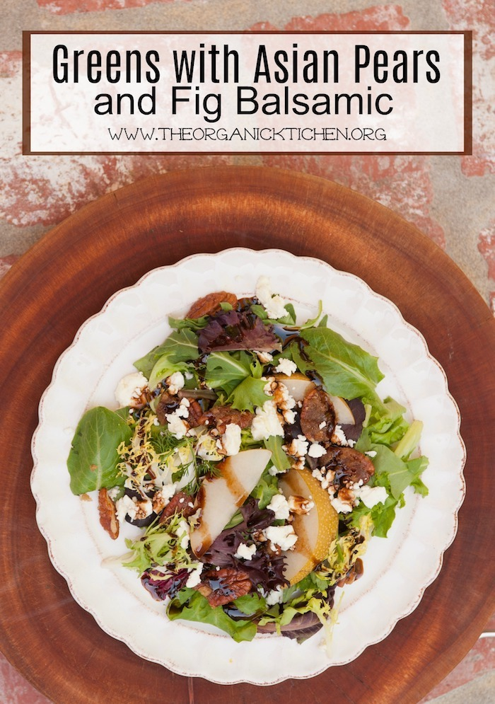 """Greens with Asian Pears and Fig/Maple Balsamic Vinaigrette"" on a white plate with scalloped edges set on a wooden cutting board"