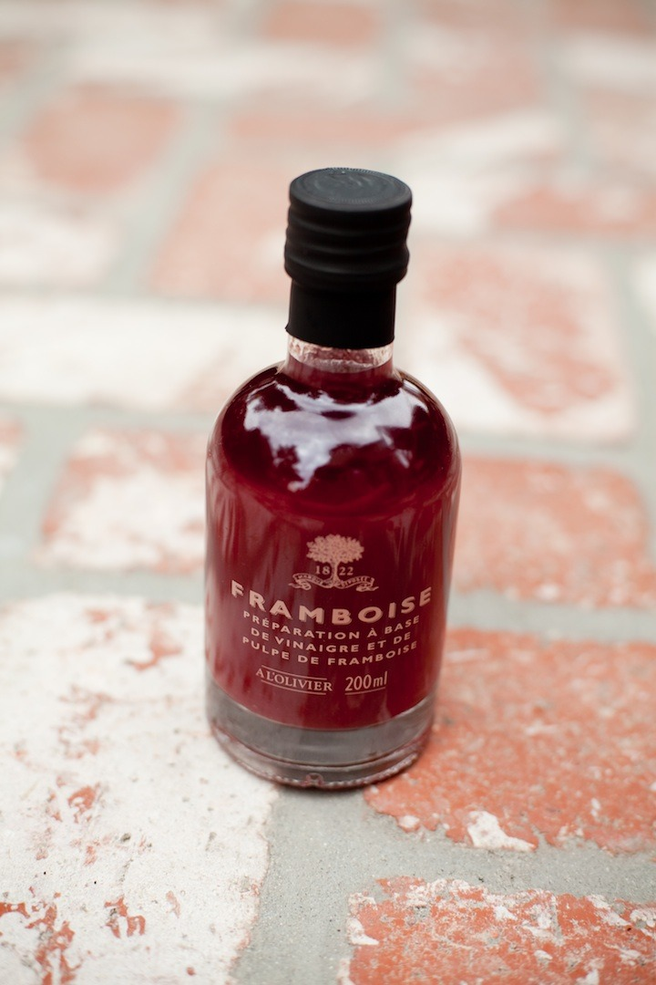 A bottle of raspberry vinegar on brick surface