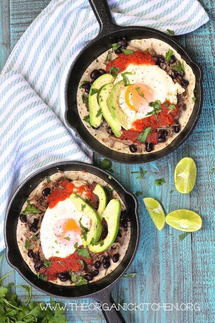 An aerial view of two pans filled with Easy Huevos Rancheros, a stripped dish towel, and lime wedges