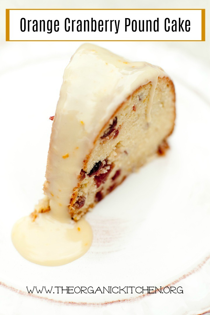 A slice of Orange Cranberry Pound Cake drizzled with orange glaze on white plate