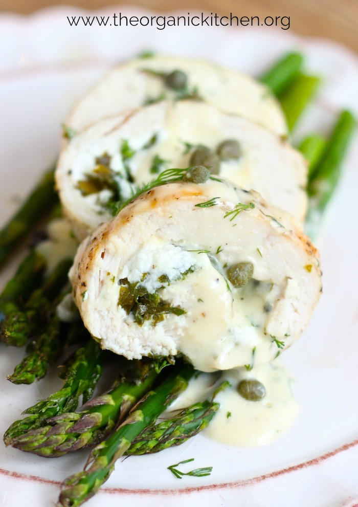 Spinach and Goat Cheese Stuffed Chicken Breasts on Asparagus with Dill Cream Sauce on small white plate garnished with dill and capers