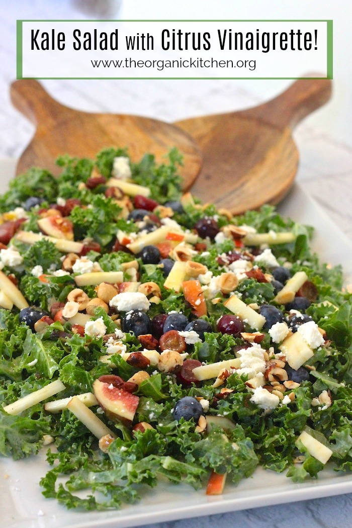 Kale Salad with Citrus Vinaigrette on large white platter with wooden salad tongs