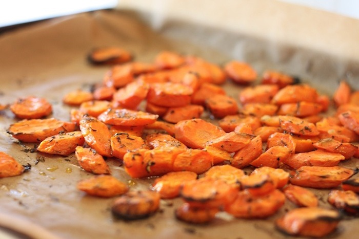 Roasted carrots on parchment covered cookie sheet for use in Baby Spinach Salad with Roasted Carrots and Israeli Couscous