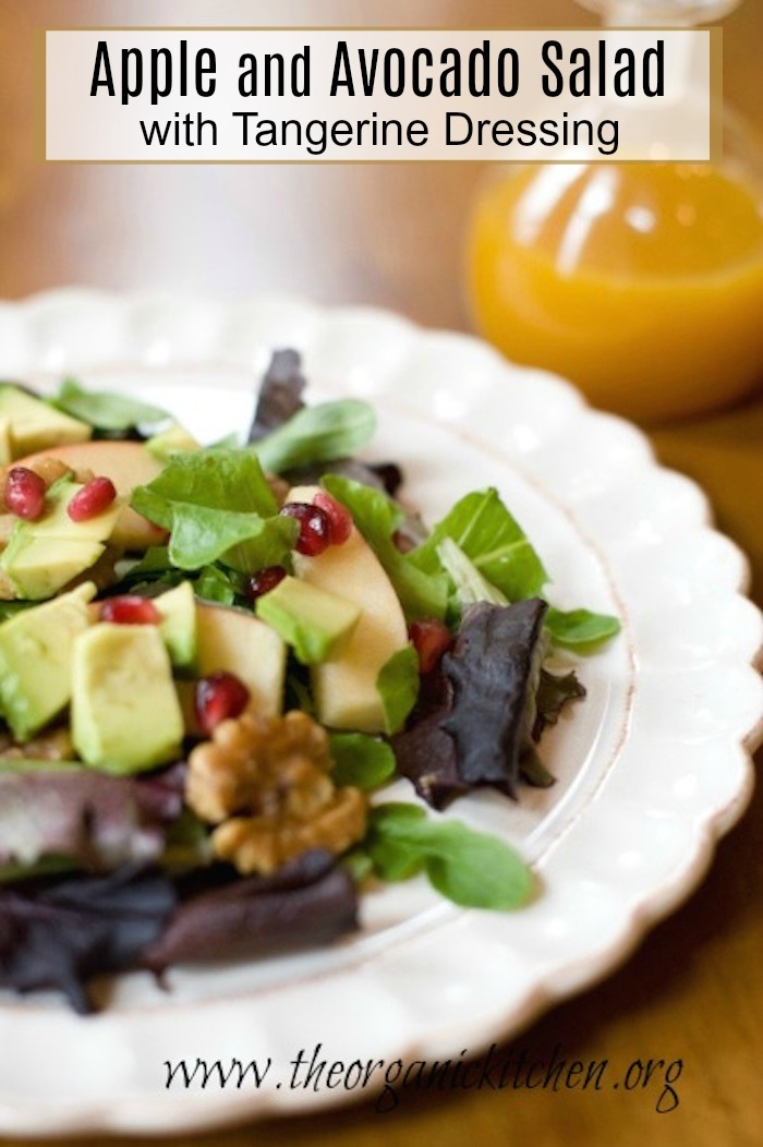 Apple and Avocado Salad with Tangerine Dressing on white plate set on wood table with a bottle of dressing in the background