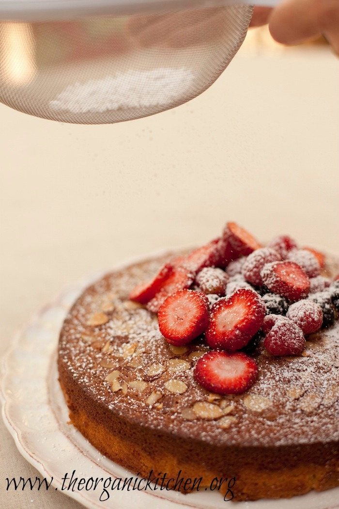 Traditional Olive Oil Cake with berries being dusted with powdered sugar