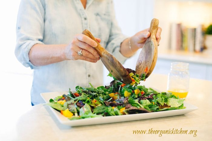 A woman using two wooden tongs to toss Greens with Mango and Citrus Vinaigrette