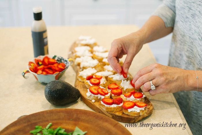 A woman placing strawberry slices on baguette slices topped with ricotta cheese to make Strawberry and Avocado Bruschetta: Bruschetta California Style!