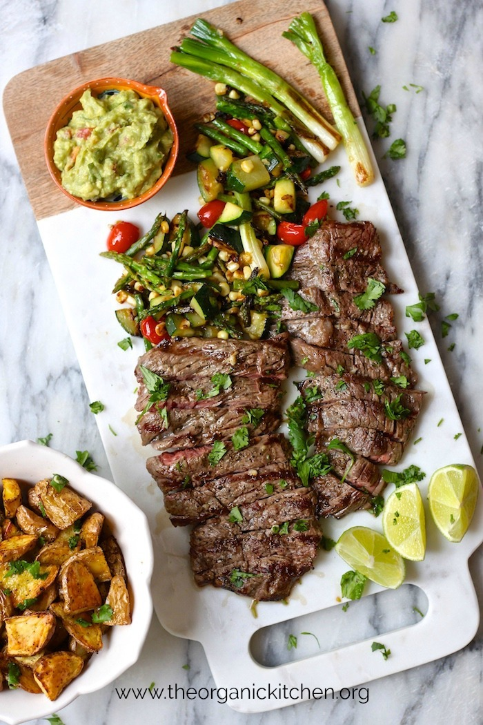 Grilled Skirt Steak and Veggies with Guacamole on a white marble cutting board