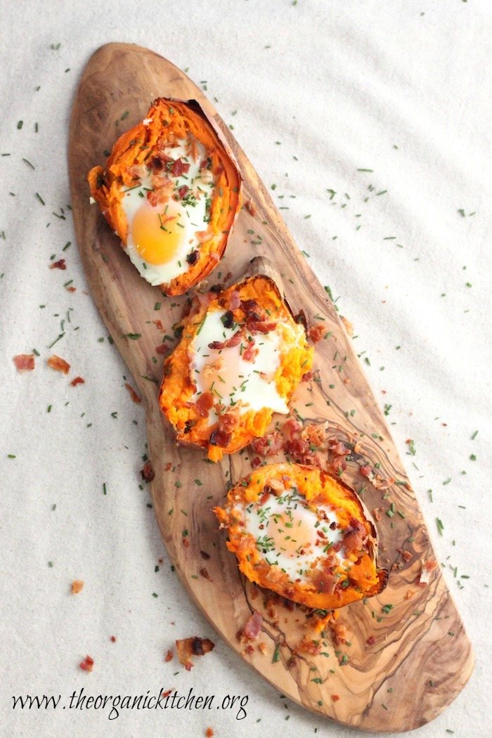 Three Twice Baked Sweet Potatoes with Bacon and Eggs on a wooden platter set on a  white cloth