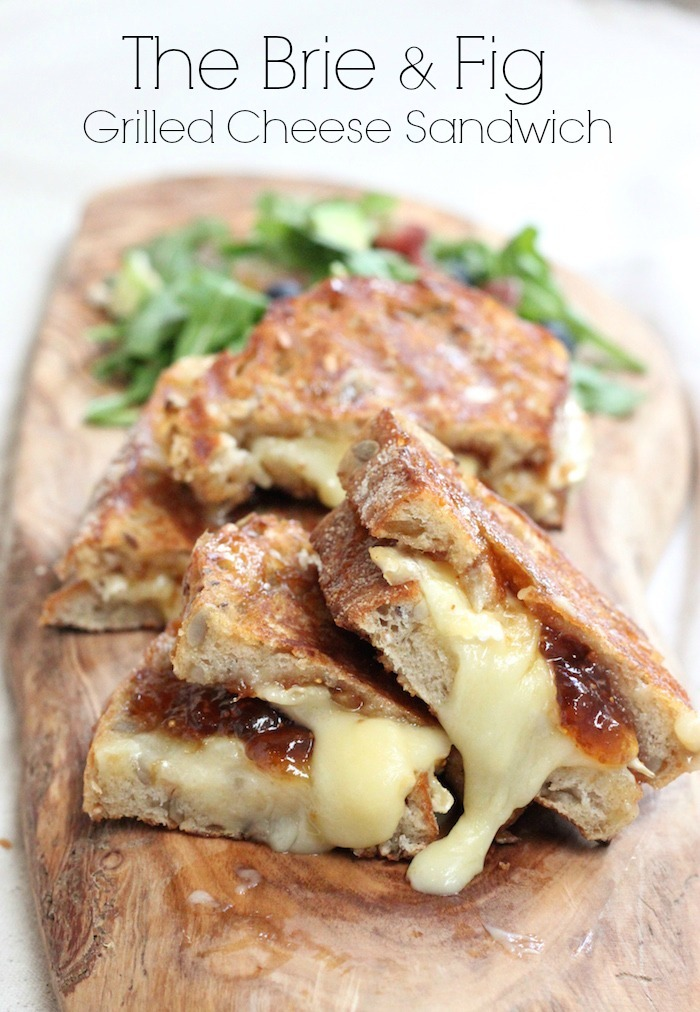 Brie and Fig Grilled Cheese on a wooden platter with greens