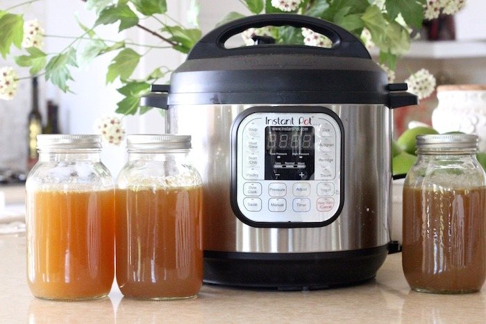 A Instant Pot with mason jars of homemade chicken broth