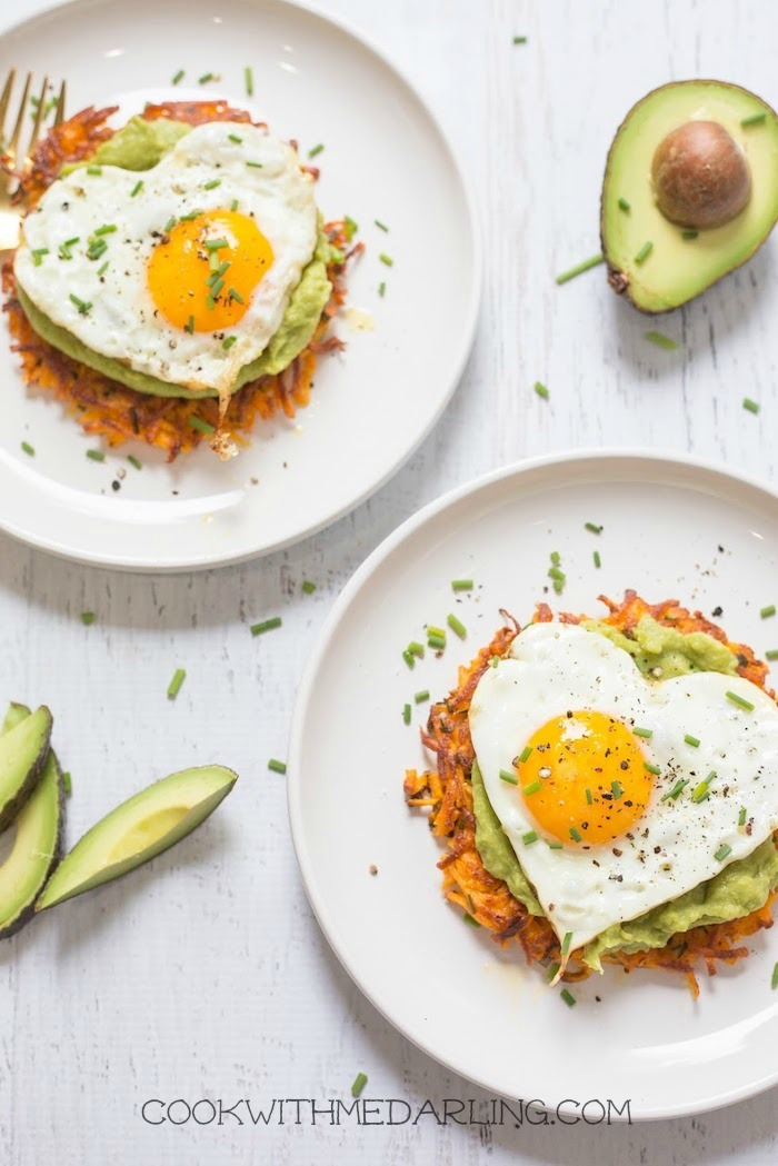 Sweet potato fritters topped with avocado mash, heart shaped fried eggs and chives on white plates, one of 12 Healthy, Delicious (Whole 30) Breakfast Recipes!