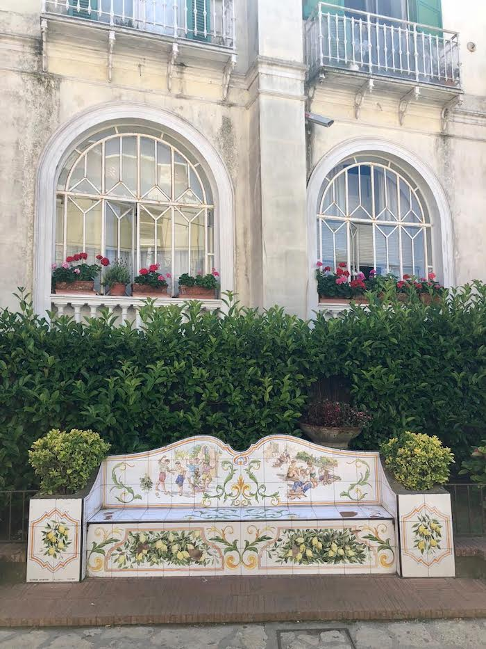 A beautiful white washed building with arched window and flower boxes  on the Island of Capri