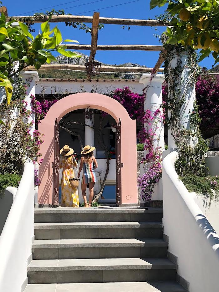 Two women in  hats and dresses under an arch on the Island of Capri