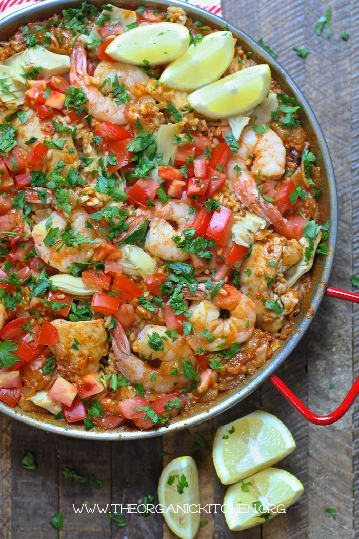 Paella Valenciana with Chicken, Chorizo and Shrimp in a paella pan surrounded by lemon wedges
