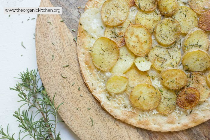 Rosemary Potato Flatbread with Cauliflower Crust Option garnished with rosemary sitting on a round wooden board