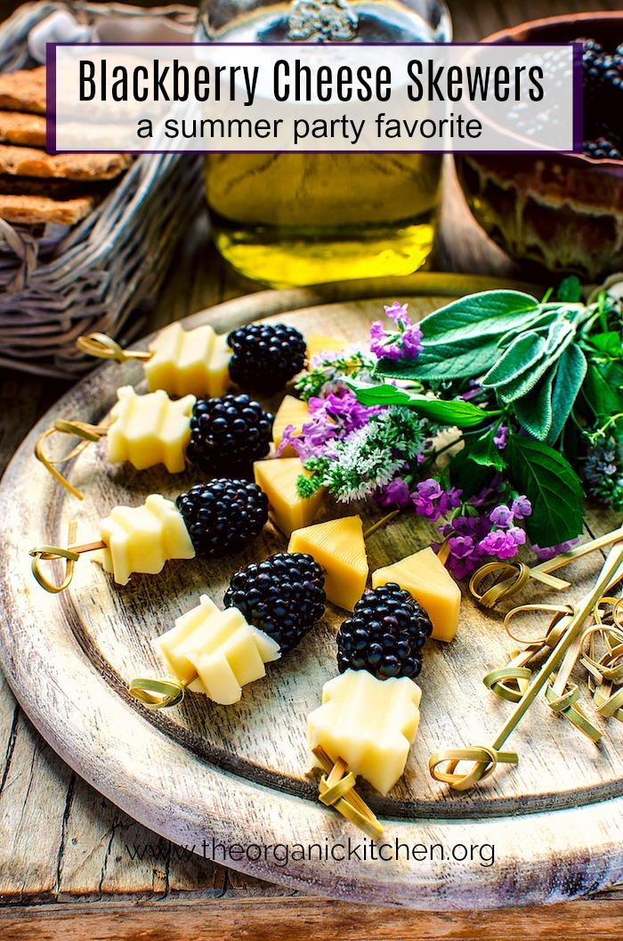 Blackberry and Aged Cheese Skewers on a round wood platter garnished with herbs and flowers