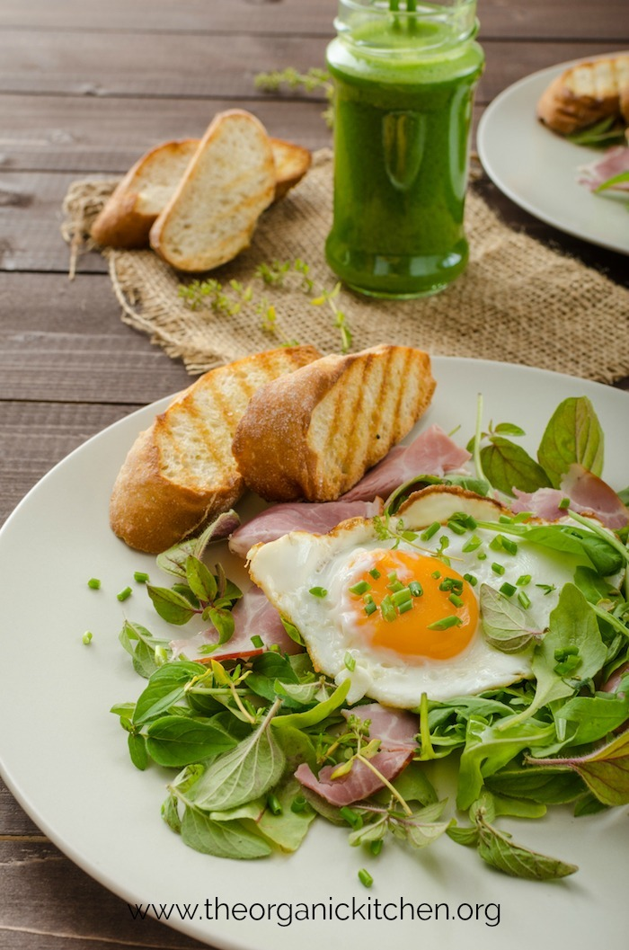 Simple Green Salad with Ham and Fried Egg on white plate with green juice and bread in background