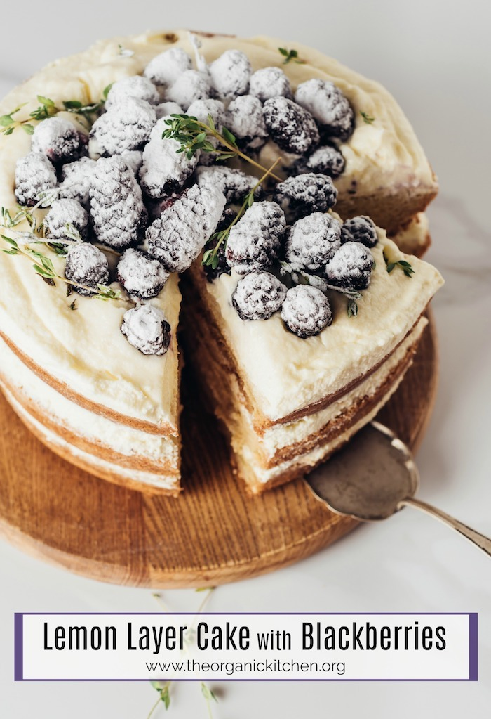 Lemon Layer Cake with Blackberries on a round wooden board with silver serving utencil