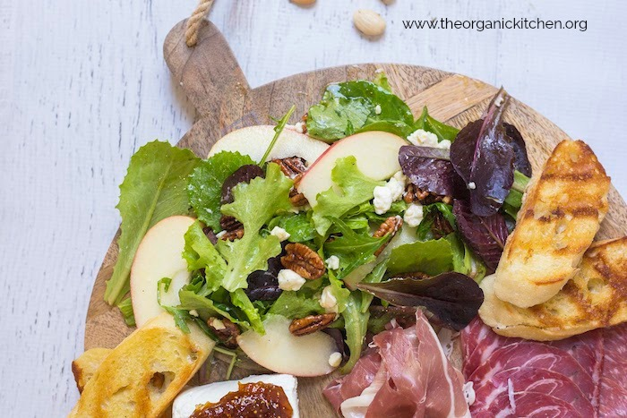 Salad and Charcuterie Board Dinner on white backdrop scattered with almonds
