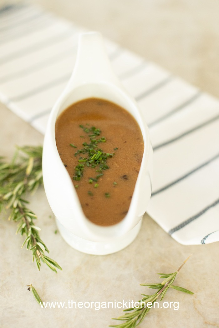 A white gravy boat filled with gray and garnished with chives: How to Make Turkey Gravy with Drippings
