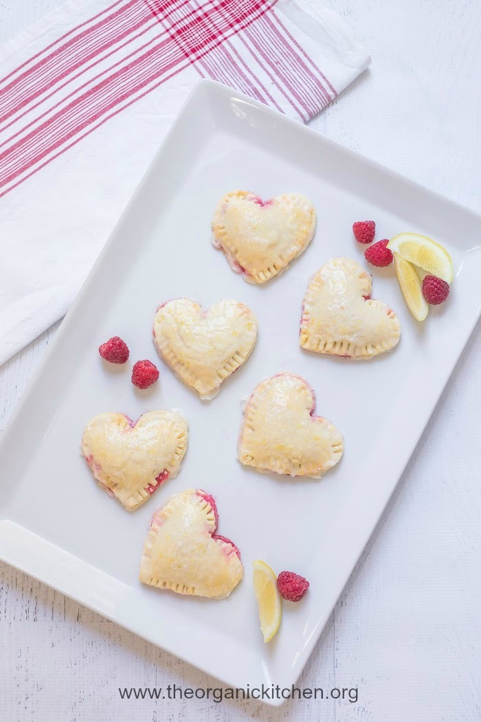 Six Raspberry-Lemon Hand Pies on white platter with red and white dish cloth