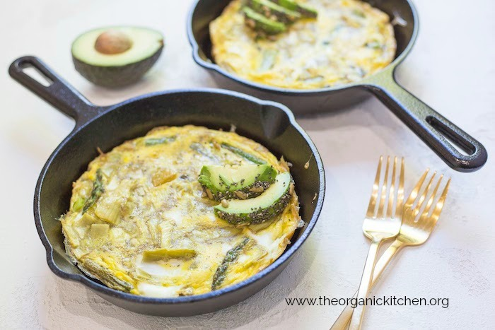 Spring Frittata with Seeded Avocado in cast iron pan with two gold forks in foreground