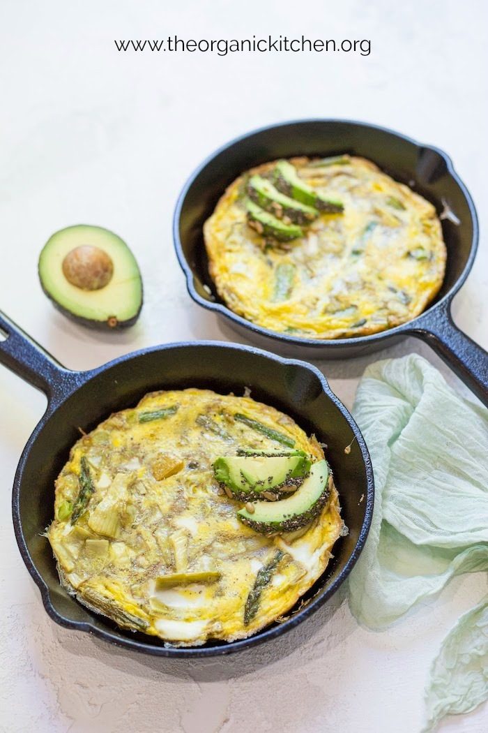 Two pans of Spring Frittata with Seeded Avocado with green cloth